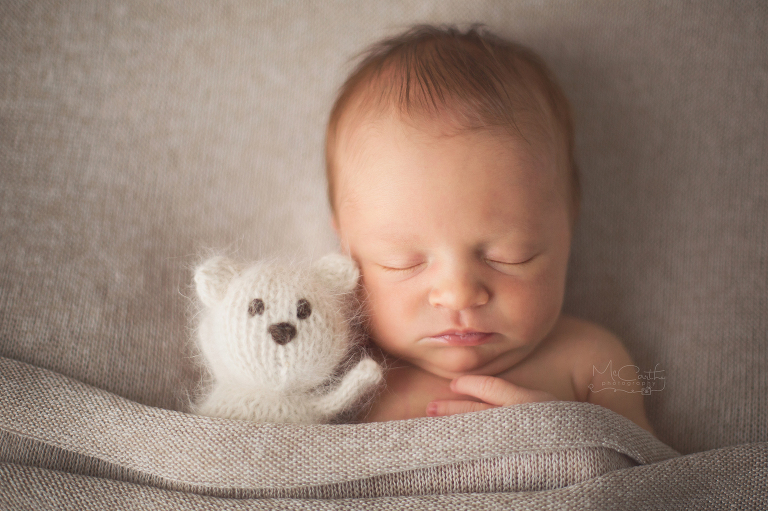 newborn baby girl with knit teddy bear