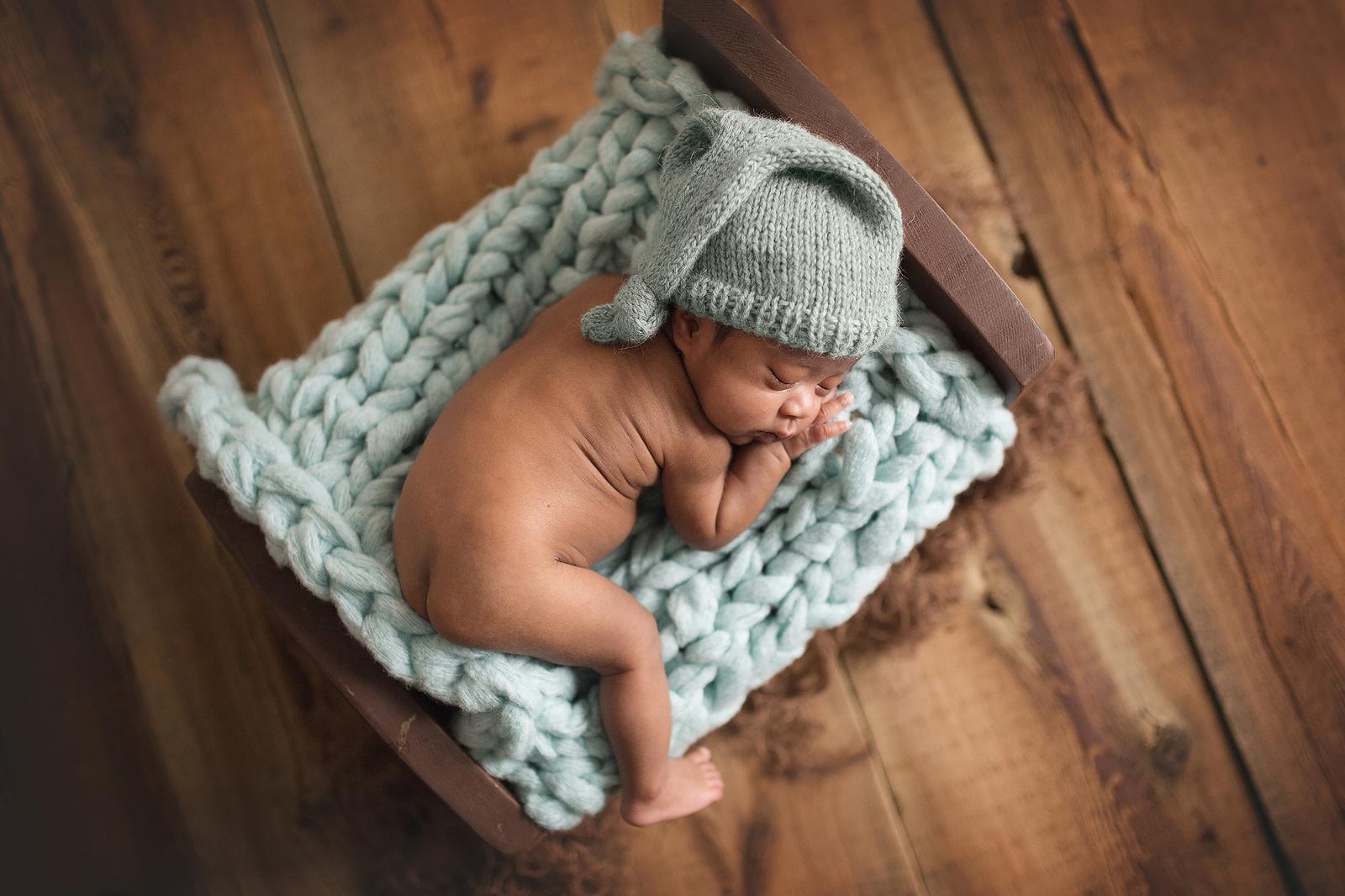 newborn baby in a sleepy hat
