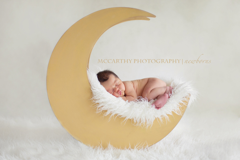 Newborn baby boy on posed on a wooden moom prop